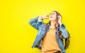 smiling-woman-looking-upright-standing-against-yellow-wall-1536619